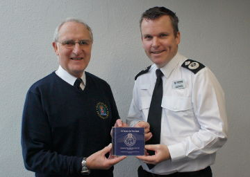 Choir Chairman Brian Wareham presenting Choir President, Deputy Chief Constable Graham McNulty with the first CD.